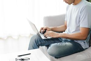 jovem sentado no sofá, digitando no laptop para trabalhar online. foto