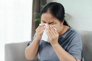 mulher doente tem alergia nasal tossir ou espirrar com lenço de papel. foto