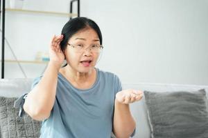 mulher surda com deficiência com problemas de audição tapar a orelha com a mão dele foto