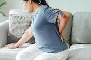 mulher sentindo dor nas costas sentada no sofá em casa foto