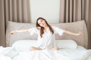 retrato de mulher bonita acordar na cama foto