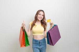 retrato de uma mulher bonita segurando uma sacola de compras e um cartão de crédito foto