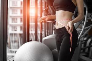 mulher desportiva usando fita adesiva na cintura no centro do clube de esporte de academia foto