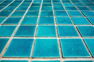 close-up do piso de ladrilho azul da piscina foto
