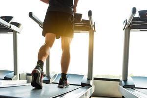 pernas de esportista correndo na esteira na academia de ginástica foto