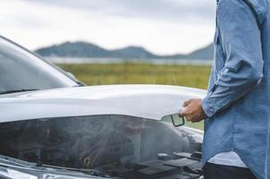 homem asiático abre o capô do carro para conserto como serviço de manutenção foto