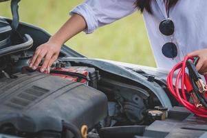closeup de uma mão de mulher segurando um cabo de bateria em um carro de conserto de fio de cobre foto