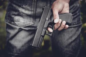 feche a mão segurando uma arma atrás foto