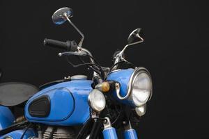 foto do close up de uma motocicleta azul vintage em fundo preto