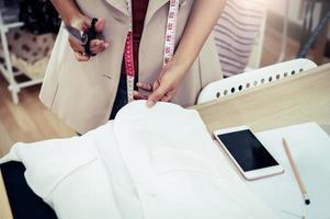 costureira cortando tecido de vestido na linha de desenho foto