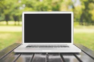 computador laptop com tela preta em branco sobre fundo verde da natureza foto