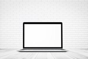 textura de parede de tijolo branco com piso de madeira e maquete de computador laptop foto