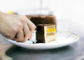 chef confeiteiro cortando bolo de chocolate caseiro foto