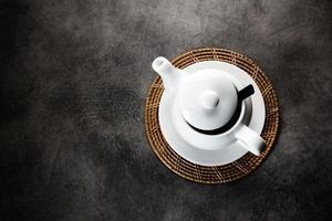xícara de chá e bule de porcelana branca foto