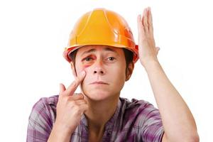 trabalhadora com um olho roxo no capacete foto