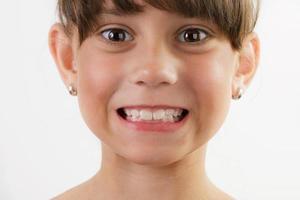 menina alegre e fofa mostra os dentes foto