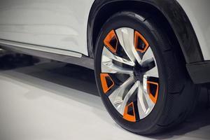 feche a roda traseira de um carro no chão branco foto