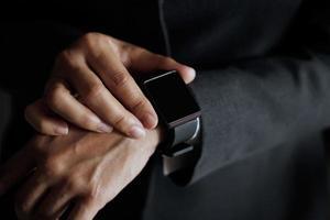 empresário pressiona o botão para encontrar emprego no relógio inteligente em mãos foto
