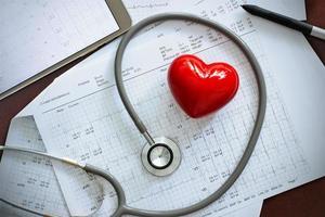 estetoscópio com formato de coração vermelho e relatório anual de exame de saúde cardíaca foto