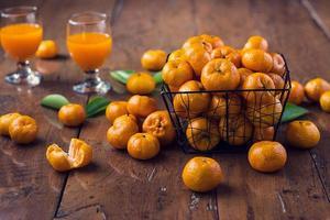 fruta laranja na cesta e copo de suco de laranja no fundo de madeira foto