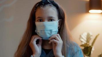 garota colocando máscara olhando para a lente da câmera foto