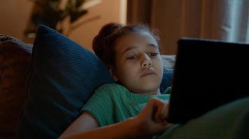 menina deitada no sofá usando o tablet foto