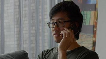 homem na sala de estar chama com celular foto