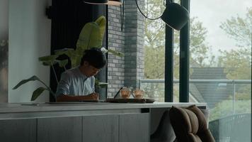 homem na mesa escreve e assiste laptop foto
