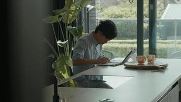 homem na cozinha fica olhando e escrevendo no caderno foto
