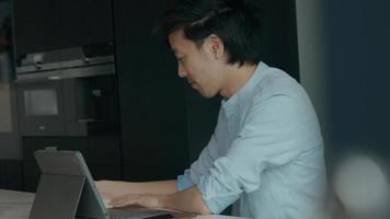 homem na cozinha com laptop olha para cima e dá de ombros foto