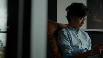 homem sentado enquanto digita no celular e olhando foto