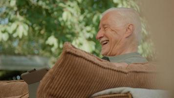 homem sentado no jardim usando um tablet enquanto fala foto