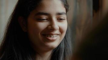 garota assistindo a um tabuleiro de xadrez falando e sorrindo foto