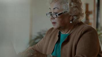 mulher sentada à mesa usando laptop e falando foto