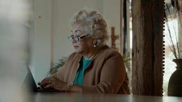 mulher sentada à mesa digitando no laptop foto