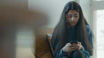 menina sentada no canto olhando para o smartphone foto