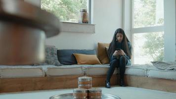 menina sentada no canto da sala digitando no smartphone foto