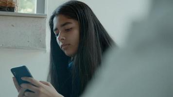 menina sentada digitando no smartphone foto