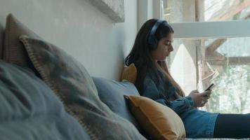jovem mulher em smartphone com fones de ouvido foto