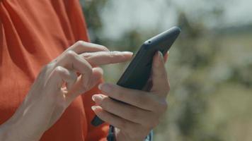 mãos de mulher em área verde digitando em smartphone foto
