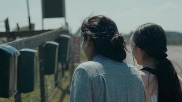 mulher e menina caminhando pelo campo vendo caixas de correio na cerca foto