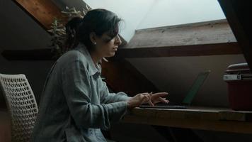 mulher sentada à mesa digitando e rolando no laptop foto