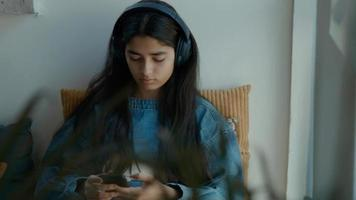 menina com fone de ouvido sentada em um canto enquanto digita no smartphone foto