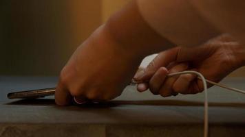 close-up do telefone celular, mãos de uma jovem conectando o cabo foto
