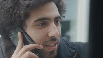 jovem homem do Oriente Médio falando vividamente, segurando o celular no ouvido foto