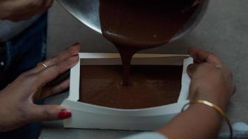 pessoa negra servindo mistura para bolo em uma forma de papel para bolo foto