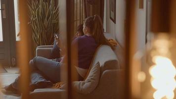 mulher assistindo menino com videogame no sofá foto
