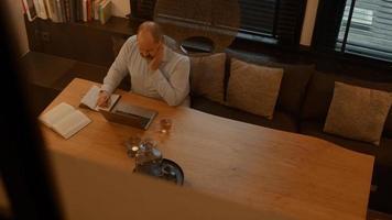 homem à mesa fazendo uma chamada online no laptop foto