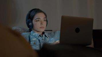 mulher no sofá com fone de ouvido assistindo laptop foto