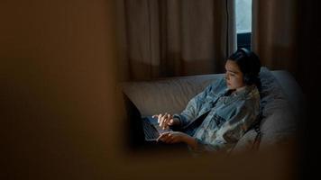 mulher no sofá com fone de ouvido rolando no laptop foto